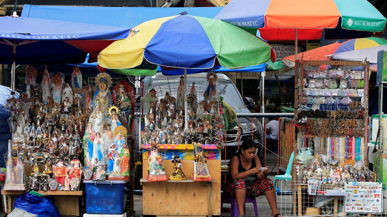 Foto: Una vendedora de iconos religiosos chequea su teléfono móvil en Manila, en mayo de 2017. (Reuters)