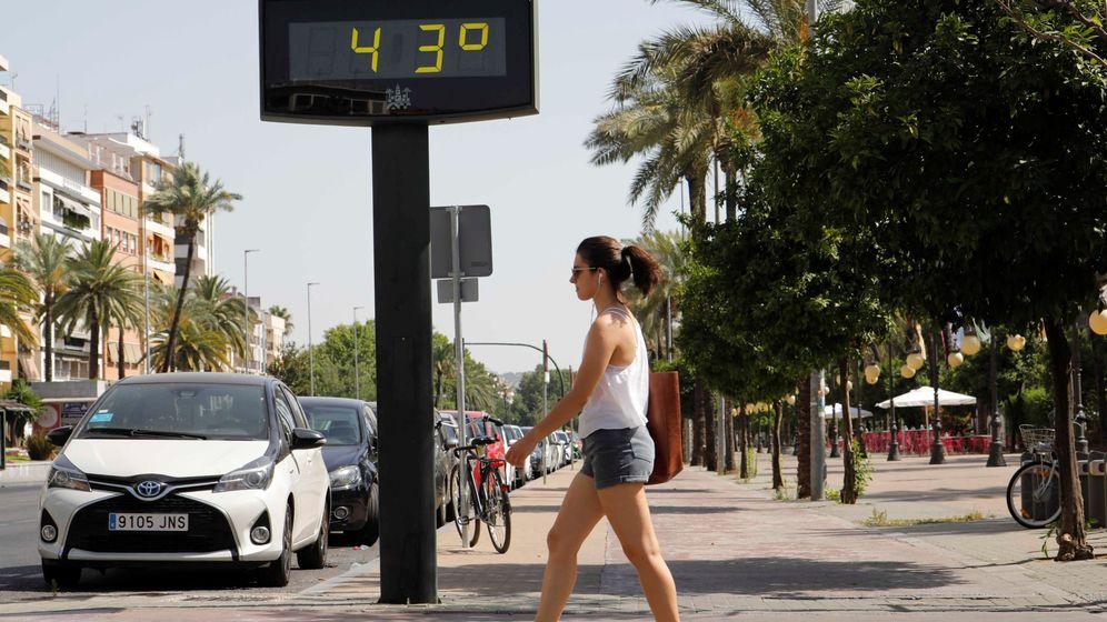 Foto: Una mujer camina junto a un termómetro que marca 43 grados. (EFE)