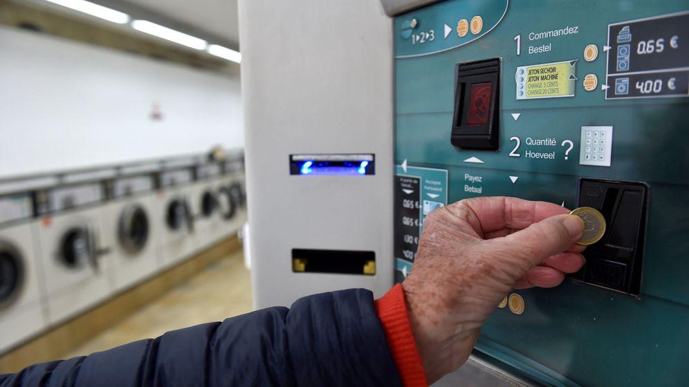 Foto: Un cliente inserta un euro en una lavandería bruselense (Eric Vidal / Reuters)