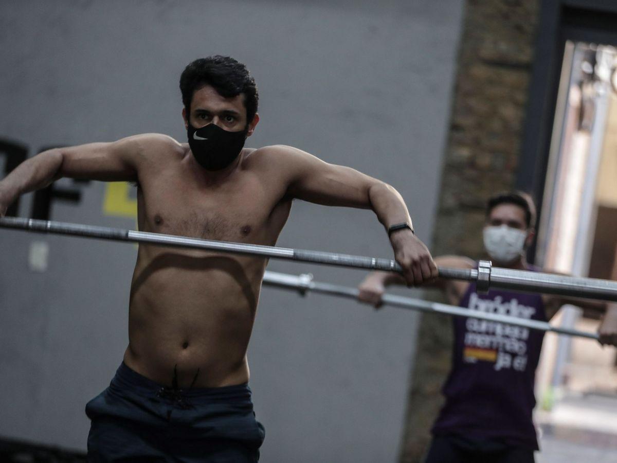 Foto: Dos hombres practican crossfit con mascarilla. (EFE)