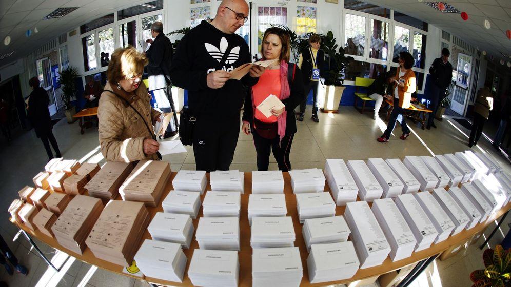Foto: Tres personas deciden su voto en un colegio electoral. (EFE)
