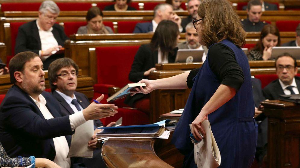 Foto: La diputada de la CUP Euilàlia Reguant le regala un libro al vicepresidente, Oriol Junqueras, durante el debate sobre los presupuestos en el Parlament. (EFE)
