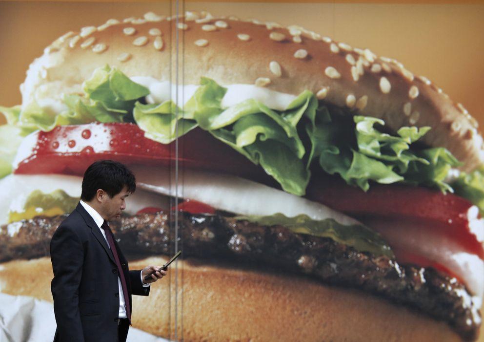 Foto: Un ejecutivo pasa frente a un anuncio de una hamburguesería en Tokio. (Reuters)