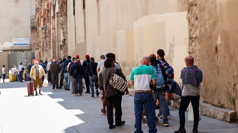 Una de las cientos de colas diarias esperando el reparto de comida solidaria. (EFE)