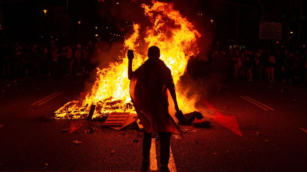 Foto: Varios manifestantes queman fotos del rey Felipe durante la protesta por la visita de la familia real a Barcelona. (EFE)