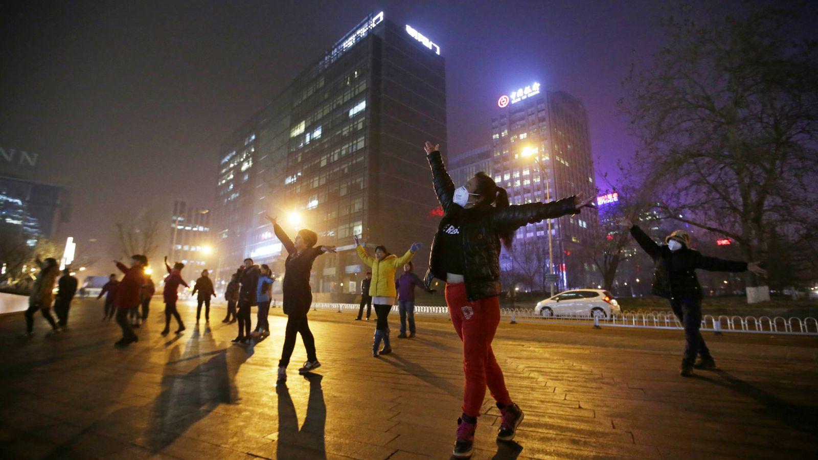 Foto: Mujeres con mascarillas para protegerse de la contaminación hacen ejercicio en Pekín, China. (Reuters)