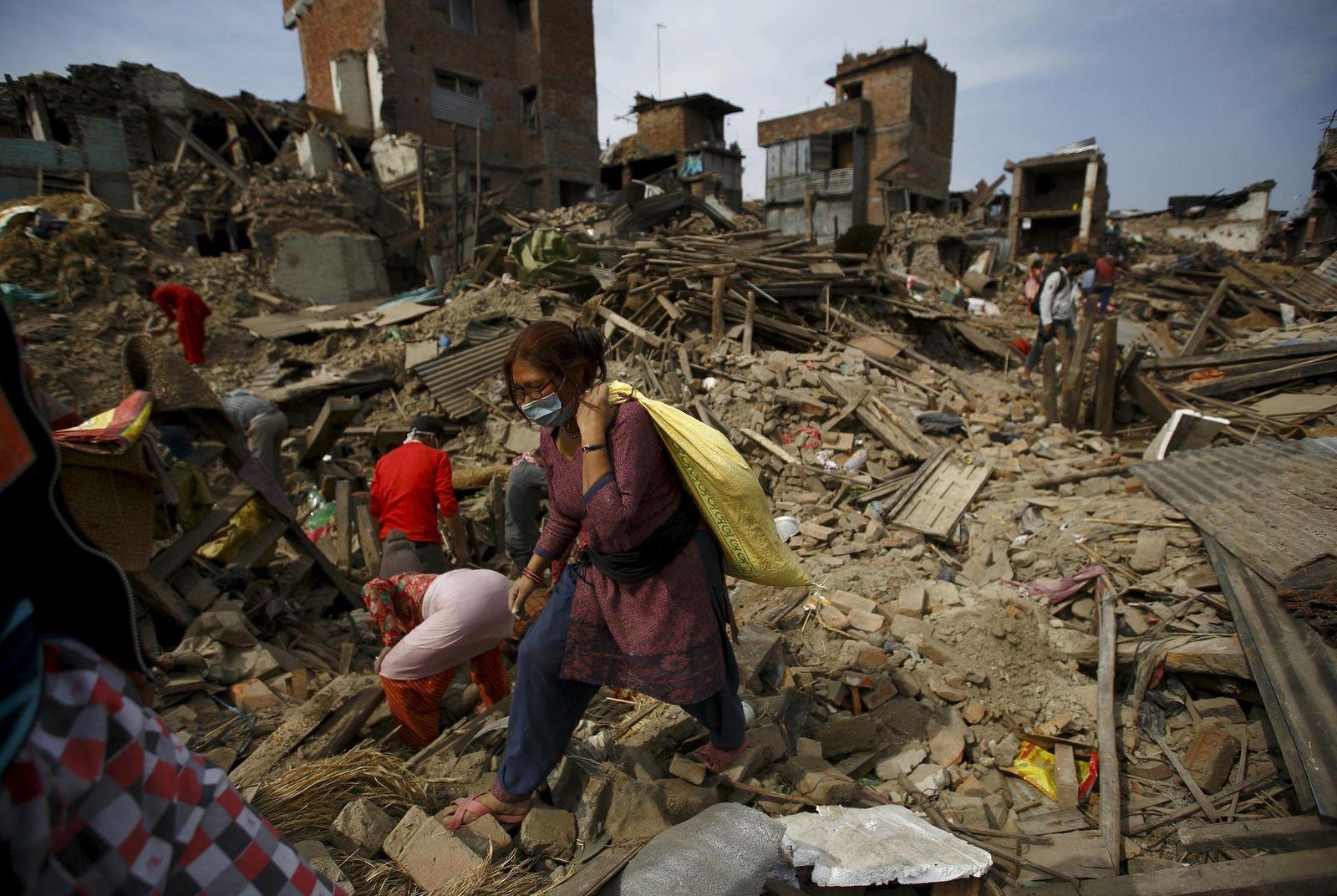 Foto: Una mujer transporta las pertenencias que ha recuperado de entre los escombros en Bhaktapur. (Reuters)