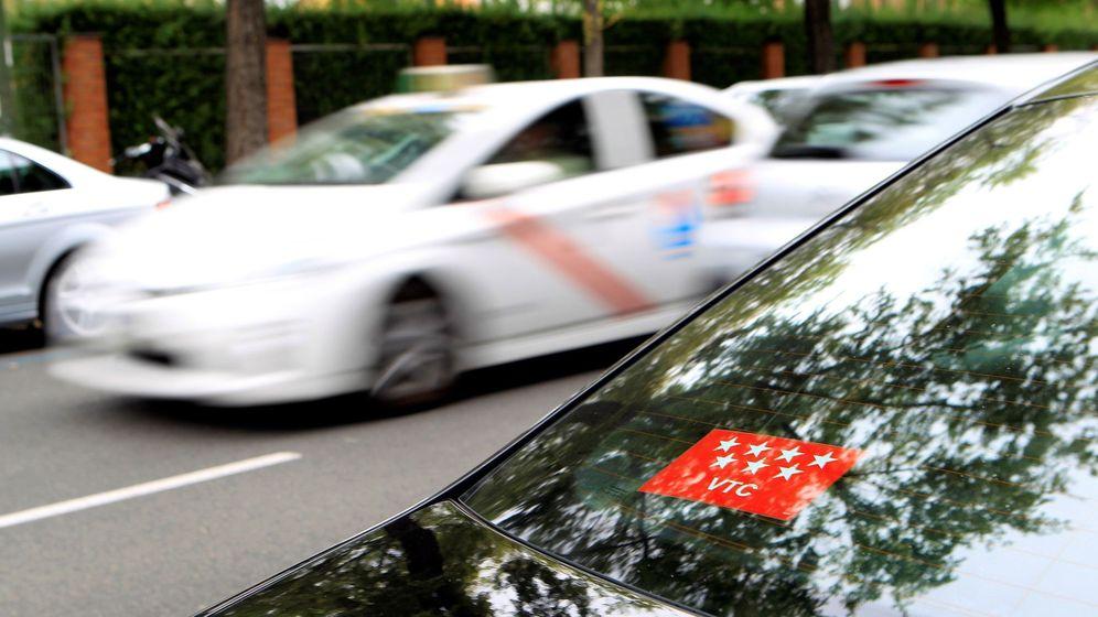 Foto: Un taxi madrileño y un vehículo con licencia VTC (EFE)