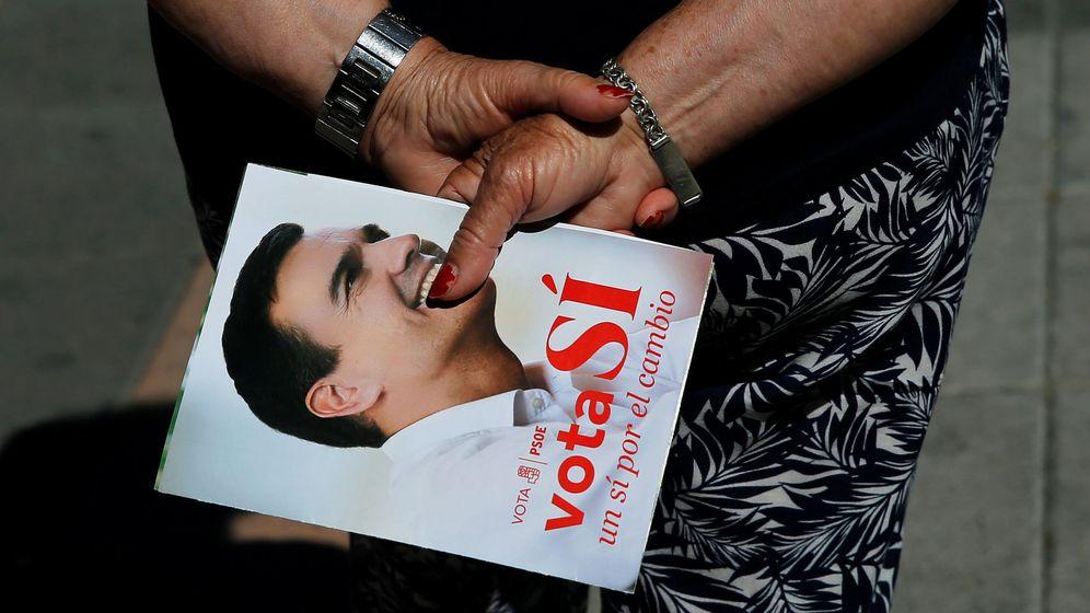 Foto: Una mujer sujeta un papel de propaganda del PSOE en la campaña de las generales del 26 de junio. (Reuters)