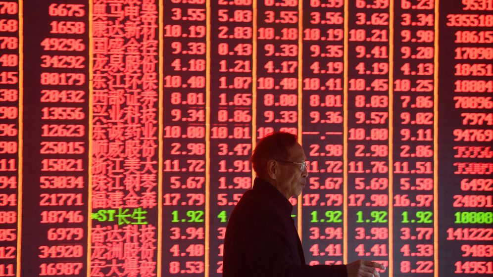 Foto: Un hombre pasa por delante de una pantalla con información financiera en Hangzhou, China, en febrero de 2019. (Reuters)