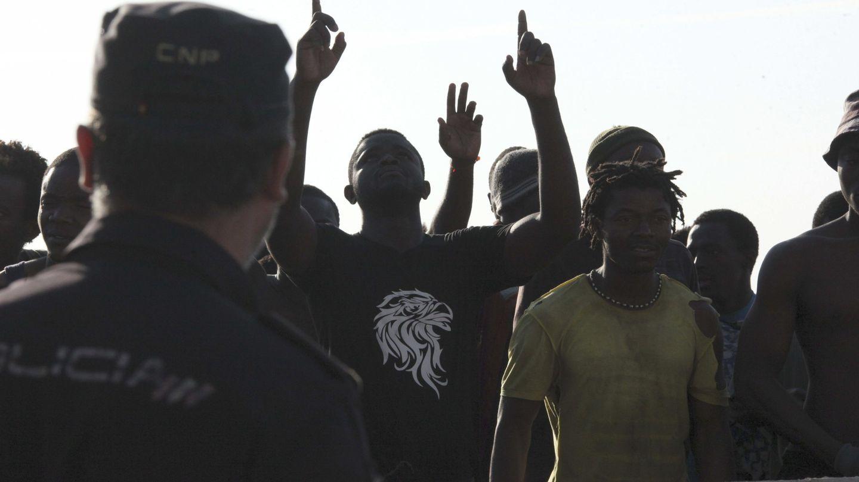 Agentes de la Policía Nacional custodian a inmigrantes subsaharianos. (EFE)
