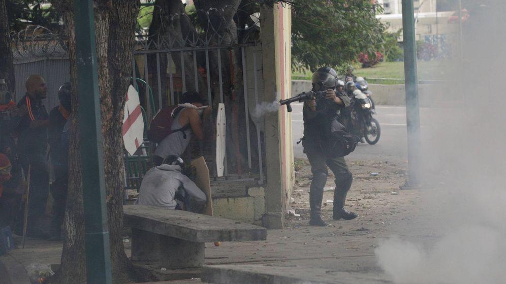 Foto: Un agente de los antidisturbios lanza una bomba de gas durante una protesta contra el Gobierno de Nicolás Maduro, en Caracas. (Reuters)