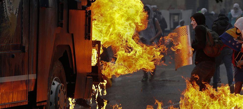 Foto: Manifestantes se protegen de las llamas cerca de un cañón de agua de la policía durante protestas en Caracas, Venezuela. (Reuters)
