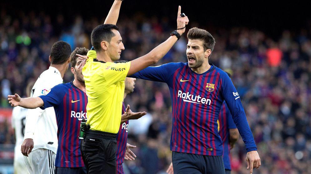 Foto: José María Sánchez Martínez calma a Gerard Piqué durante un enfrentamiento entre FC Barcelona y Real Madrid. (EFE)