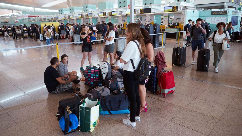 Foto: Varias personas esperan este sábado en el aeropuerto del Prat. (EFE)