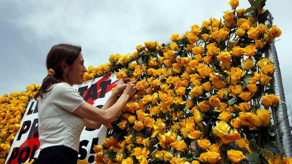 Foto: La periodista Txell Bonet, pareja del presidente de Òmnium, Jordi Cuixart, coloca una rosa amarilla el día de Sant Jordi. (EFE)