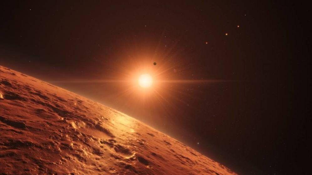 Foto: Representación artística de la superficie de uno de los planetas del nuevo sistema con la estrella TRAPPIST-1 brillando al fondo