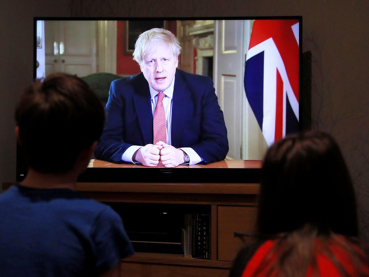 Foto: Dos niños observan el mensaje a la nación de Boris Johnson. (Reuters)