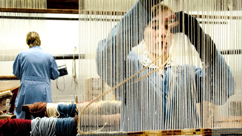 Foto: Tejedora de alfombras pasando las tramas en un momento del proceso de trabajo en la Real Fábrica de Tapices. (Corrado Bonora)