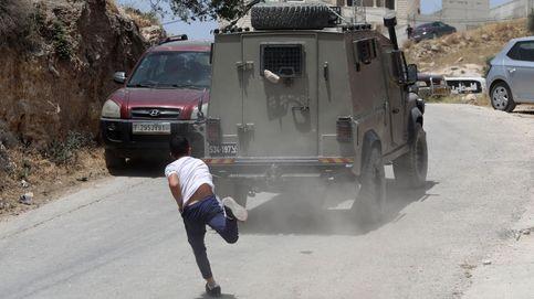 Un palestino lanza una piedra a un blindado israelí