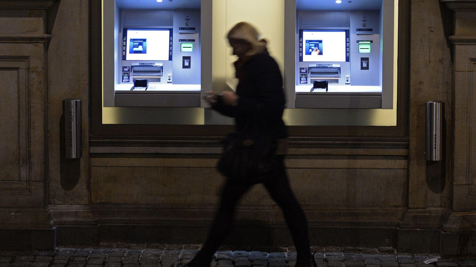 Foto: Una mujer pasa por delante de dos cajeros automáticos en Copenhague, Dinamarca, el 22 de enero de 2015 (Reuters)