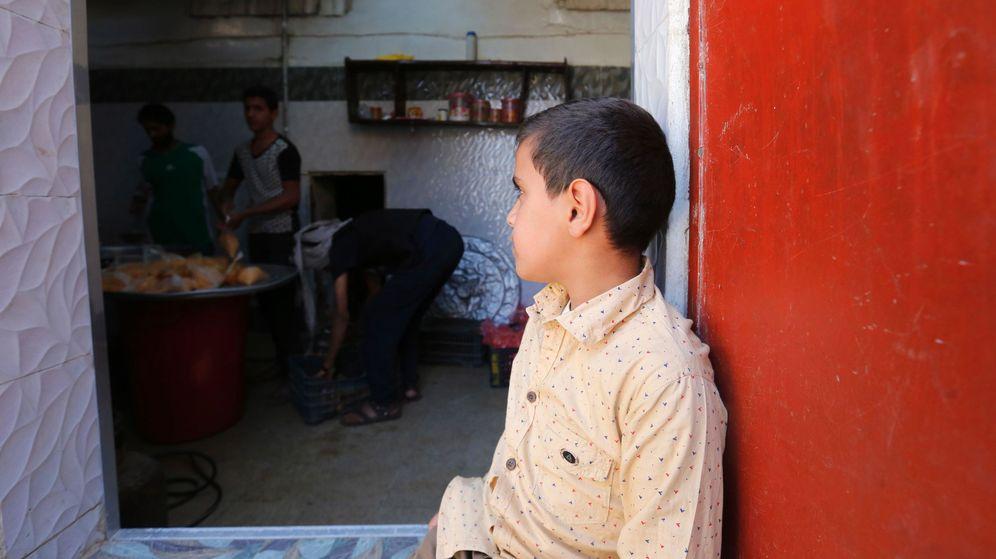 Foto: Un niño observa a voluntarios mientras preparan raciones de comida para yemeníes afectados por la guerra, en Saná (Yemen). Foto: EFE
