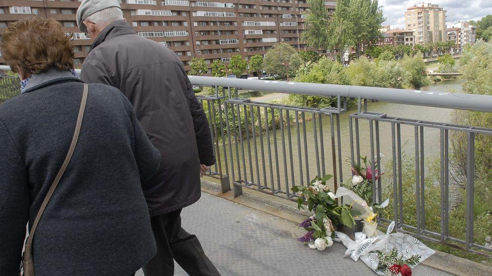 Foto: Dos personas pasan junto a flores depositadas en la pasarela en la que fue asesinada la presidenta de la Diputación de León, Isabel Carrasco. (EFE)
