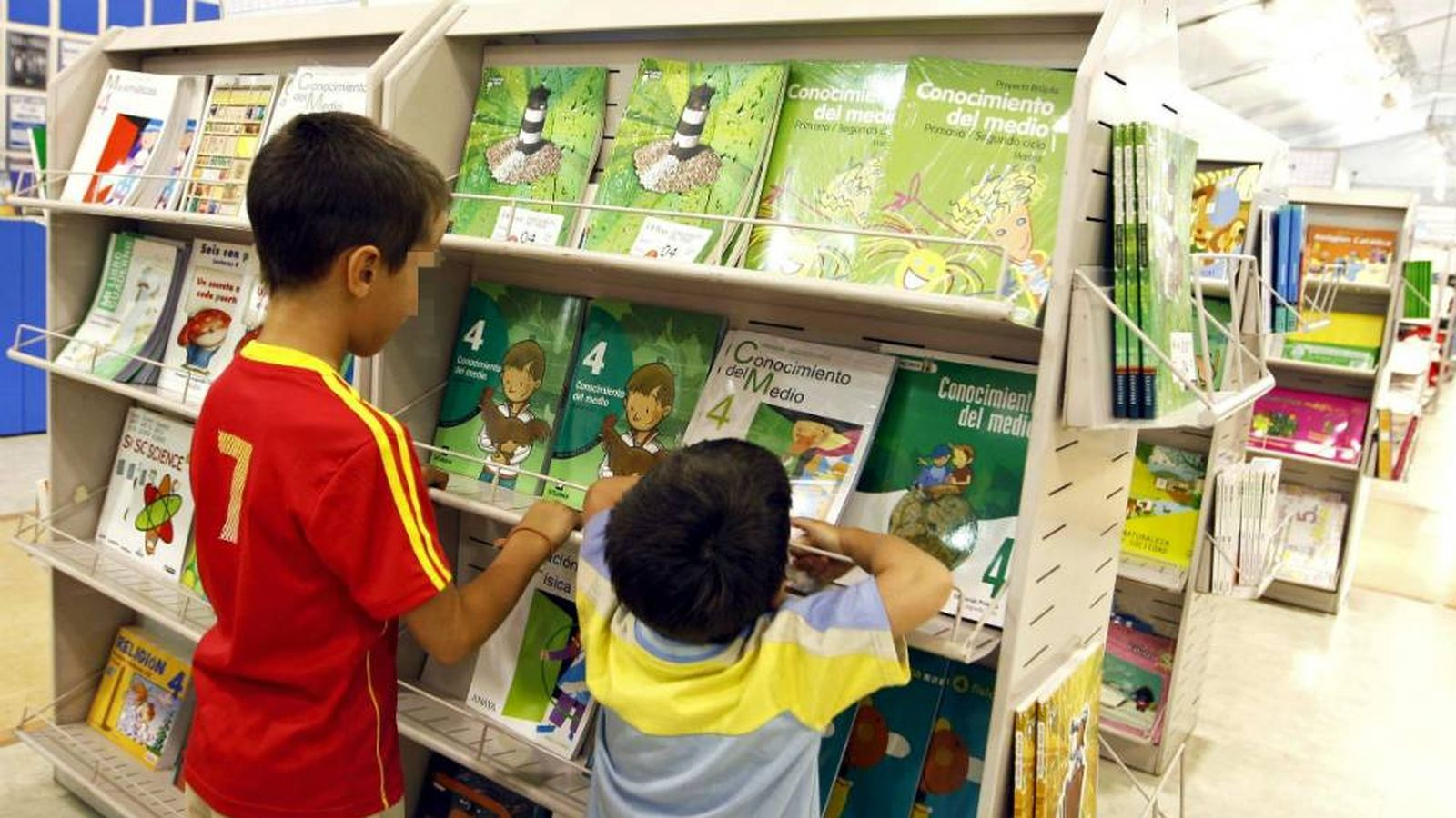 Foto: Dos niños buscan sus libros de texto en un gran superficie. (EFE)