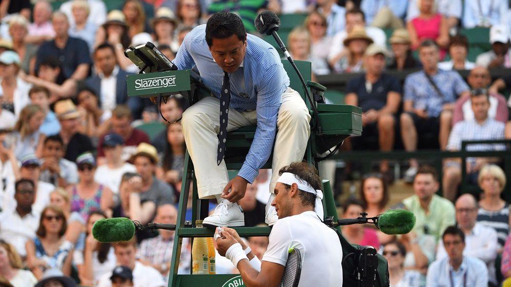 Foto: Nadal, enseñando las ampollas de su mano al árbitro tras recibir un 'warning' en Wimbledon. (EFE)