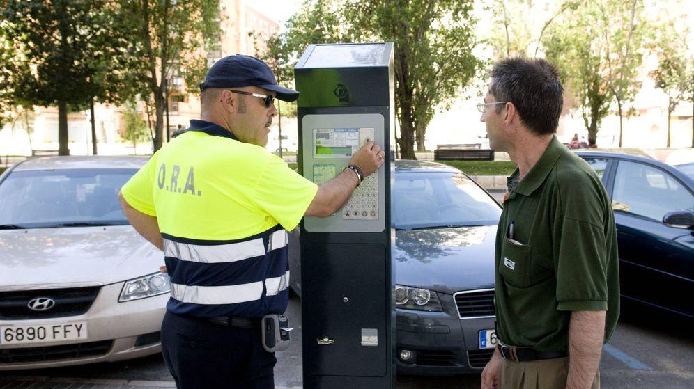 Foto: Un controlador de un parquímetro, atendiendo a un conductor.