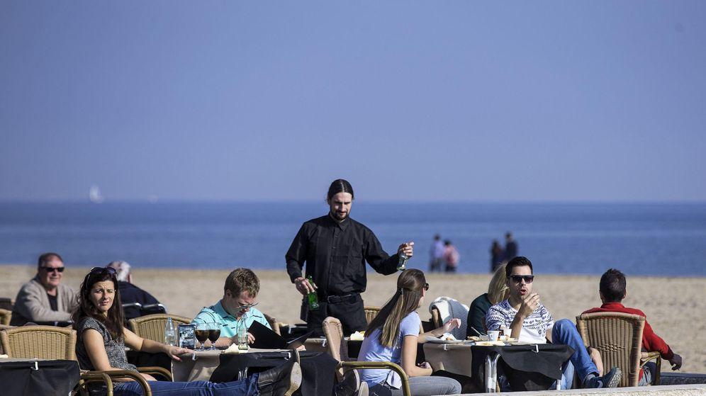 Foto: Varias personas disfrutan de las temperaturas suaves tomando un aperitivo en una terraza en la playa de La Malvarrosa de Valencia. (EFE)