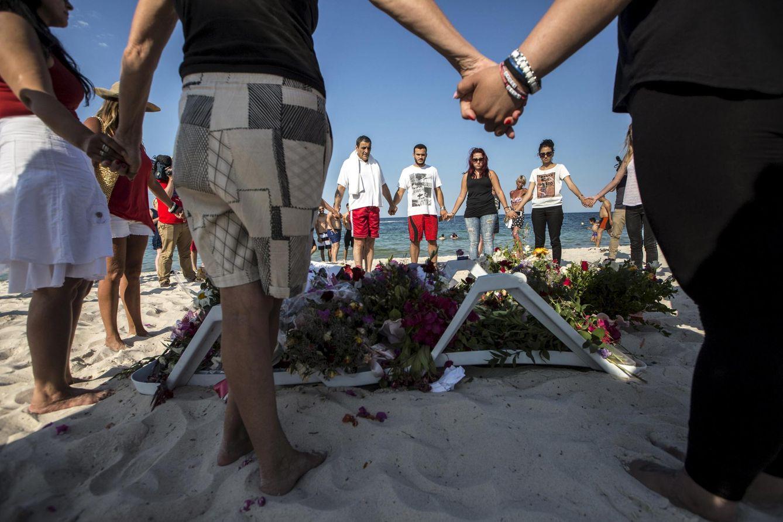 Foto: Un grupo de personas forma un círculo en torno a unas flores en tributo a las víctimas del ataque de Susa, en Túnez. (Reuters)