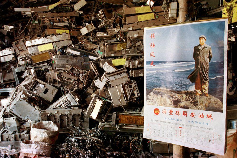 Foto: Basura tecnológica apilada tras un poster de Mao Zedong en la aldea de Yaocuowei, en el sur de China, en 2002. (Reuters)