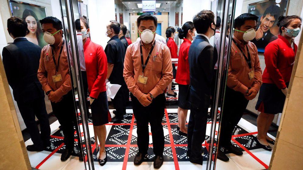 Foto: Empleados de oficina se protegen con mascarilla mientras esperan el ascensor sobre un cuadrante dibujado. (EFE / Rungroj Yongrit)