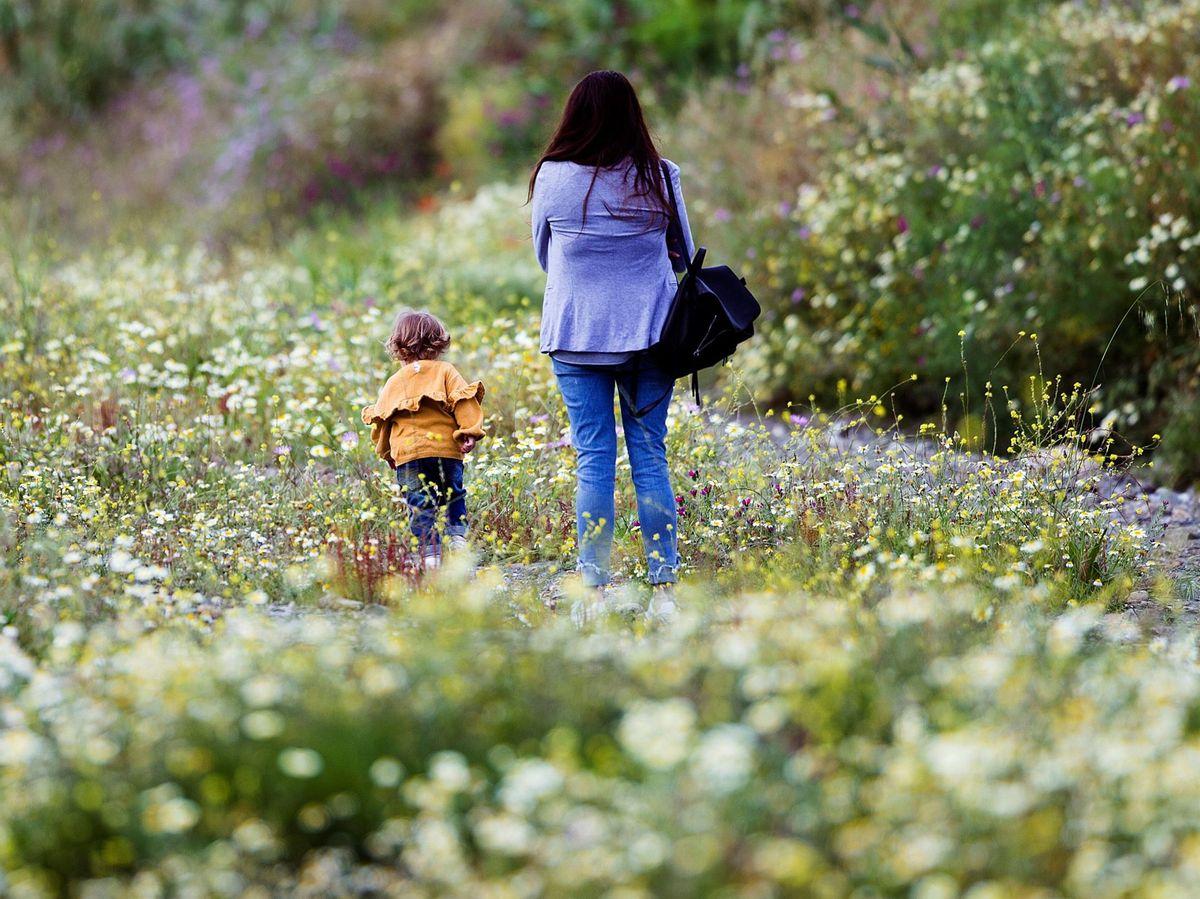 Foto: Una mujer pasea con una menor en el Rincón de la Victoria, Málaga (EFE)
