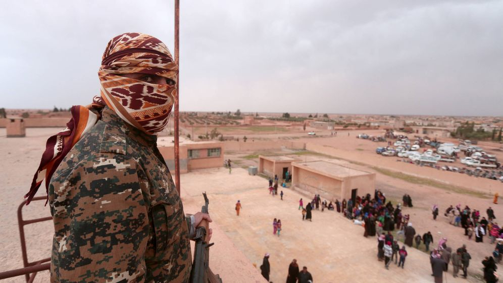 Foto: Un combatiente de las milicias kurdo-árabes SDF observa a civiles que huyen de Raqqa cerca de la ciudad. (Reuters)