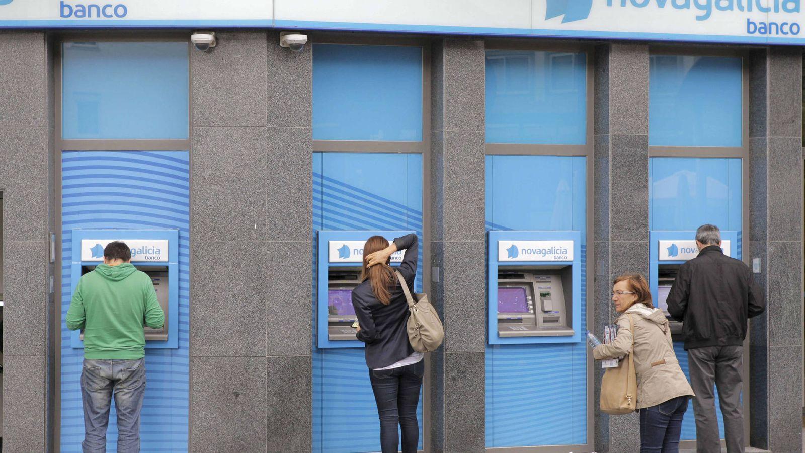 Foto: Fotografía de archivo de una sucursal bancaria en Santiago de Compostela, donde varios usuarios retiran dinero del cajero. (EFE)