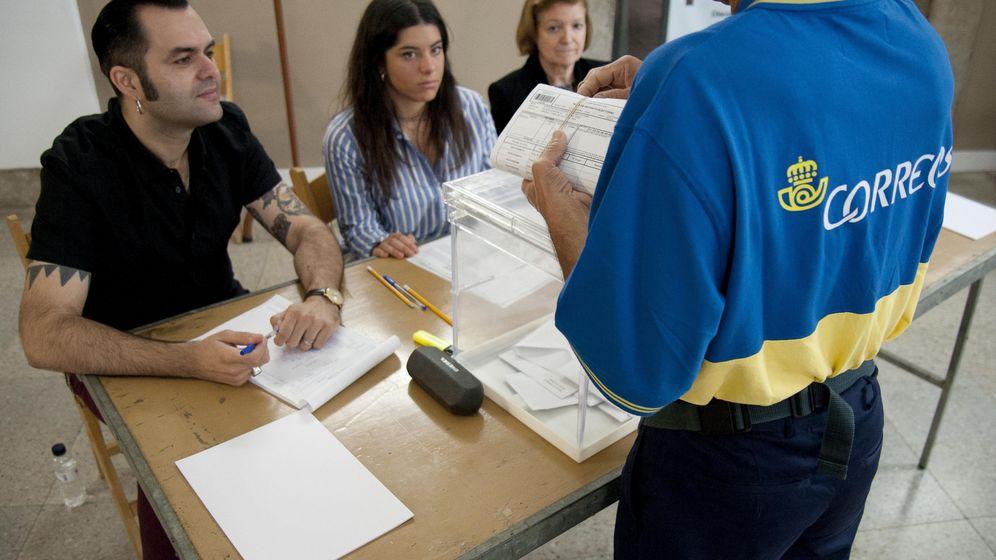 Foto: Un funcionario de Correos entrega en una mesa electoral varios votos por correo. (EFE)