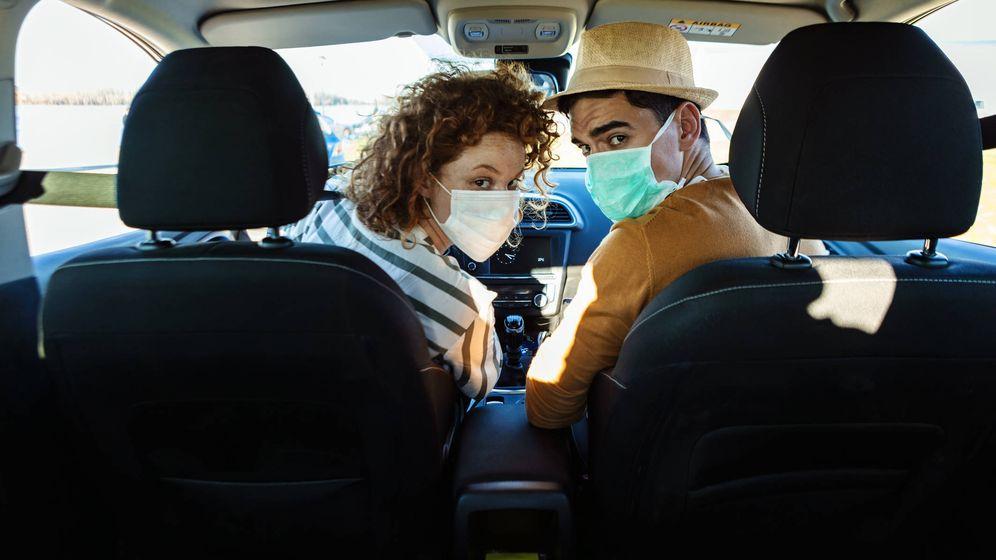 Foto: La conductora y el copiloto de un coche, con mascarillas. (iStock)