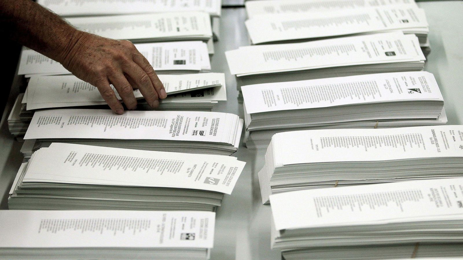 Foto:  Un ciudadano coge una papeleta en un colegio electoral del centro de Barcelona. (EFE)