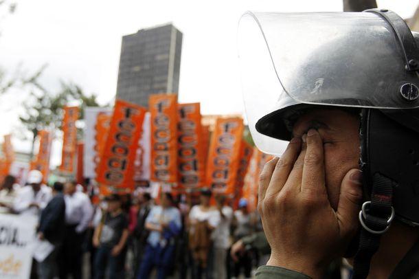 Foto: Un policía antidisturbios se frota los ojos durante una marcha de profesores en Bogotá, en una imagen de archivo. (Reuters)