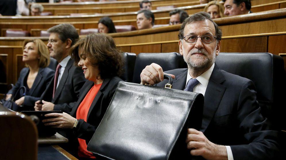 Foto: El presidente del Gobierno, Mariano Rajoy, sostiene su cartera en el Congreso de los Diputados. (EFE)