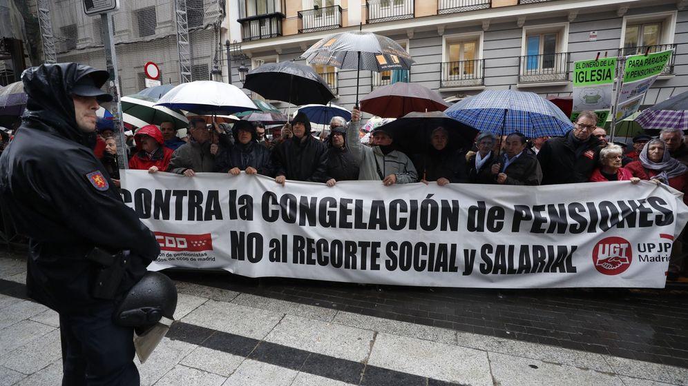 Foto: Centenares de jubilados exigen bajo la lluvia una subida digna de su pensión. (EFE)
