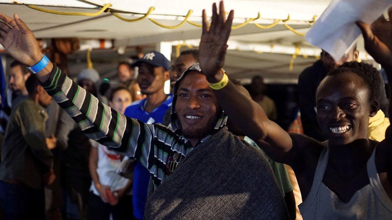 Algunos de los migrantes que quedaban a bordo del barco de la ONG española Open Arms saludan momentos antes de desembarcar. (EFE)