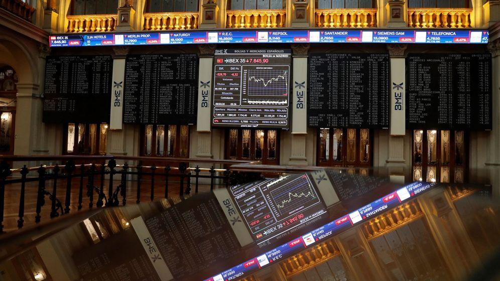 Foto:  Una pantalla (al fondo) muestra un gráfico con la evolución del IBEX 35 en la Bolsa. (EFE)