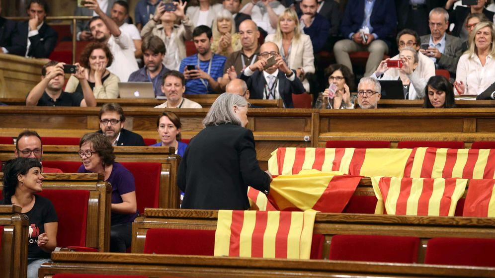 Foto: La diputada de Catalunya Sí Que Es Pot Àngels Martínez retira las banderas de España de los escaños del PPC, este 6 de septiembre. (EFE)