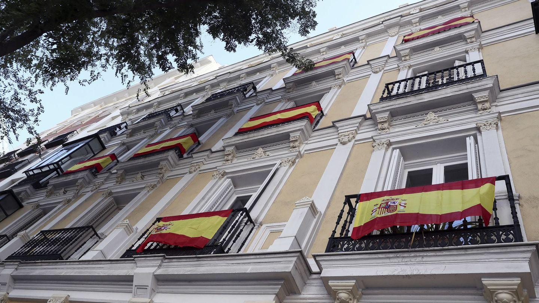 Algunas banderas de España lucen en balcones de la calle Almagro de Madrid. (EFE)