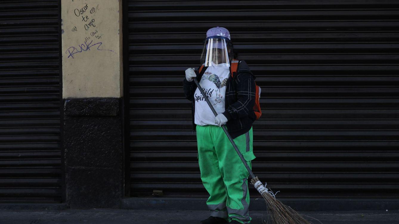 Foto: Personal de limpieza se protege con un casco. (EFE)