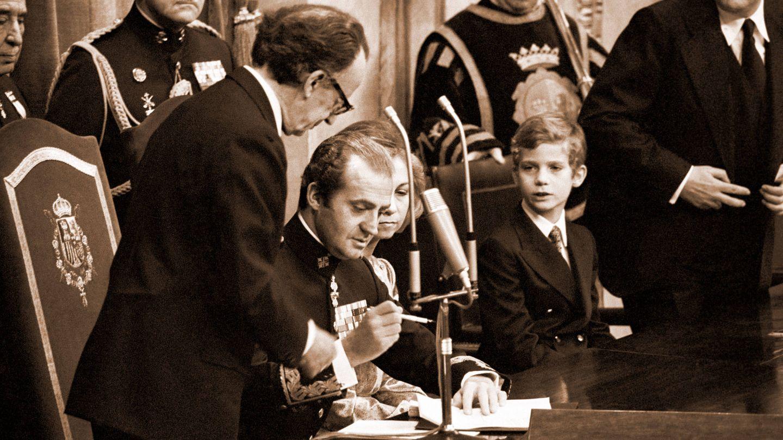 El Rey, a punto de firmar el documento, en presencia del príncipe Felipe. (EFE)