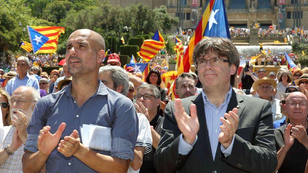Foto: Pep Guardiola, junto a Carles Puigdemont, aplaude al finallizar un acto con el lema 'Referéndum es democracia'. (EFE)